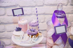 Candy bar. Table with sweet candies, purple light at background